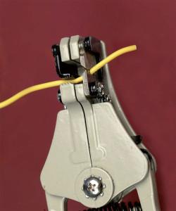 Figure-2-19. Lorsque vous utilisez des pinces coupantes automatiques (ici, un modèle américain) et que vous appuyez sur les branches, la mâchoire de gauche serre le fil et les rainures de droite mordent sur la gaine isolante. Serrez plus fortement pour que les mâchoires s'éloignent en séparant l'isolant du fil.